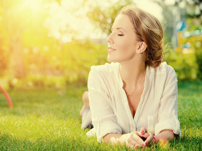 Beautiful smiling woman lying on a grass outdoor. She is absolut